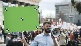Gente europea en la demostración Hombre con una bandera que grita en una boquilla almacen de metraje de vídeo