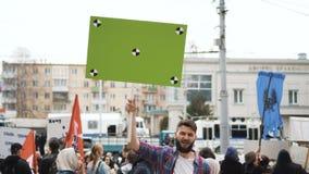 Gente europea en la demostración Hombre con una bandera que grita en una boquilla