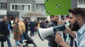 Gente europea en la huelga Hombre con una bandera que grita en una boquilla 4k