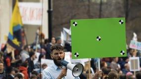 Gente europea en la reunión Hombre caucásico con la bandera que grita en una boquilla metrajes