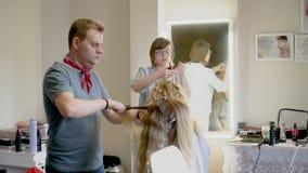 Gente europea sul lavoro nel primo piano del salone del ` s del parrucchiere stock footage