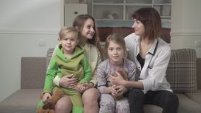 Gente felice allegra di famiglia di quattro che si siede insieme sul sofà Festa della famiglia video d archivio