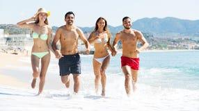 Gente felice che corre alla spiaggia Immagini Stock