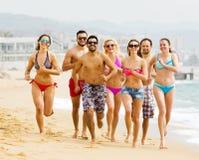 Gente felice che corre alla spiaggia Fotografie Stock