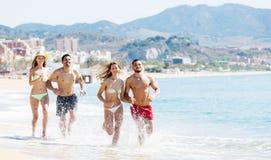 Gente felice che corre alla spiaggia Fotografia Stock