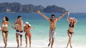 Gente felice che corre dalle mani di ritenzione di acqua sui bei amici del gruppo della spiaggia, dell'uomo e della donna sulla v stock footage