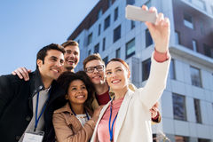 Gente felice con i distintivi di conferenza che prendono selfie Immagine Stock