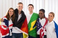 Gente felice con le bandiere dai paesi differenti Fotografia Stock Libera da Diritti