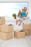 Gente felice con una pianta conservata in vaso nella loro nuova casa Fotografia Stock