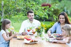 Gente felice di famiglia di quattro che gode insieme del pasto all'aperto Immagini Stock Libere da Diritti
