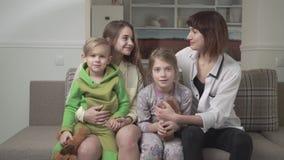 Gente feliz alegre de la familia de cuatro miembros que se sienta en el sofá junto Día de fiesta de la familia almacen de metraje de vídeo