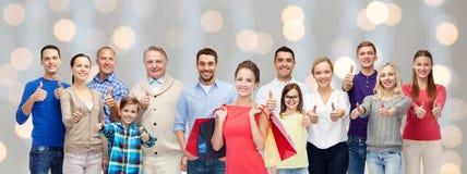 Gente feliz con los panieres que muestran los pulgares para arriba Foto de archivo libre de regalías