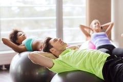 Gente feliz que dobla los músculos abdominales en fitball Foto de archivo