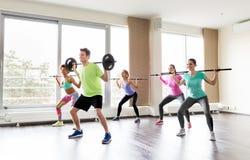 Gente feliz que ejercita con las barras del barbell en gimnasio Fotografía de archivo libre de regalías