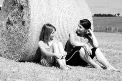 Gente feliz que habla en naturaleza en las balas de heno Fotografía de archivo libre de regalías