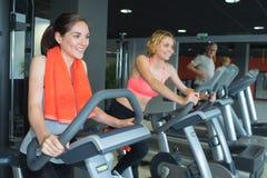 Gente feliz que hace biking interior en club de fitness imagen de archivo