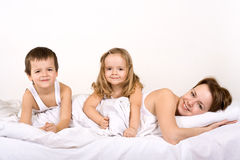 Gente feliz que presenta para un retrato de la familia en cama Imagen de archivo