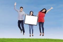 Gente feliz que salta con el tablero en blanco Fotografía de archivo libre de regalías
