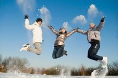 Gente feliz que salta en invierno Fotos de archivo