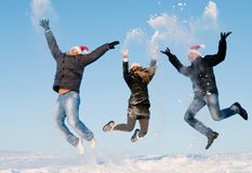 Gente feliz que salta en invierno Imagen de archivo libre de regalías