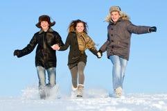 Gente feliz que se ejecuta en invierno Imagen de archivo