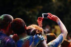 Gente feliz que toma la foto del selfie en móvil en el fest del holi, festiva Fotos de archivo