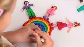 Gente feliz sobre el arco iris hecho de la arcilla de modelado metrajes