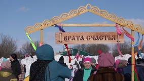 Gente fotografiada cerca de la puerta de la felicidad durante Maslenitsa - día de fiesta religioso, popular ruso