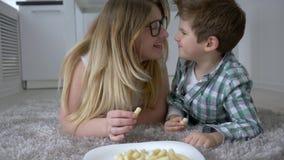 Gente hambrienta, niño agradable con la madre que come los dulces que mienten en piso en casa almacen de video