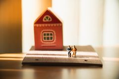 Gente, hombre miniatura y mujer sentándose en casa Imagenes de archivo