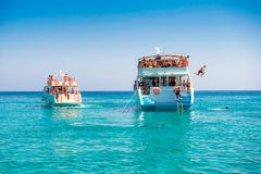 Gente indefinible que salta de un barco turístico de la travesía en el mediterráneo Fotos de archivo libres de regalías