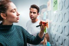 Gente inteligente de los compañeros de trabajo brainsorming el nuevo plan empresarial fijado en una pared de cristal pegajosa de  foto de archivo