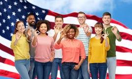 Gente internazionale che mostra okay sopra la bandiera americana Immagini Stock