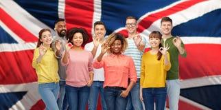 Gente internazionale che mostra okay sopra la bandiera di britannici Fotografie Stock Libere da Diritti