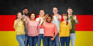 Gente internazionale che mostra okay sopra la bandiera tedesca Immagini Stock Libere da Diritti
