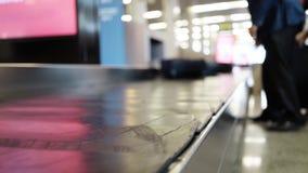 Gente irreconocible que toma su equipaje de la banda transportadora en aeropuerto almacen de video