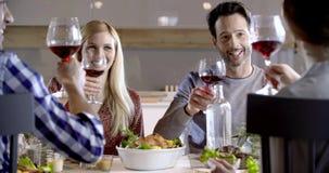 Gente italiana que hace la tostada así como el vino rojo Cuatro amigos sinceros reales felices gozan el cenar almuerzo o juntos almacen de metraje de vídeo