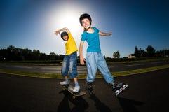 Gente joven activa - el rollerblading, andando en monopatín Imágenes de archivo libres de regalías