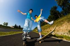 Gente joven activa - el rollerblading, andando en monopatín Foto de archivo libre de regalías
