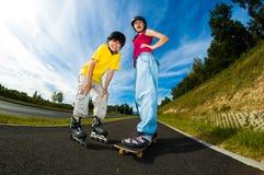 Gente joven activa - el rollerblading, andando en monopatín Fotos de archivo