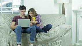 Gente joven alegre que se sienta en el sofá y metrajes