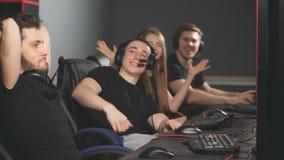 Gente joven alegre que se sienta en los ordenadores potentes en centro del juego y que da altos cinco triunfante almacen de video