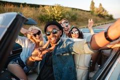 Gente joven alegre que toma el selfie en el coche Imagen de archivo libre de regalías