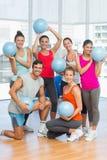Gente joven apta con las bolas en sala de ejercicio Foto de archivo libre de regalías