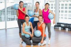 Gente joven apta con las bolas en sala de ejercicio Imágenes de archivo libres de regalías