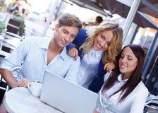 Gente joven con el ordenador portátil Imagenes de archivo