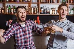 Gente joven con fútbol de observación de la cerveza en una barra Imagen de archivo