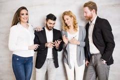 Gente joven con la tableta digital por la pared Foto de archivo