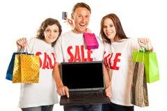 Gente joven con las camisetas y el ordenador portátil del ` de la venta del ` Imagenes de archivo