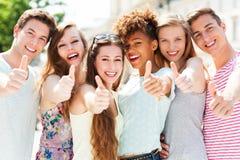 Gente joven con los pulgares para arriba Imagen de archivo